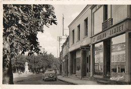 36. CPSM. AIGURANDE. Une Rue, Commerces Arnaud Jammet, Imprimerie Roger Rault, Voiture Ancienne Décapotable, 1957. - Francia
