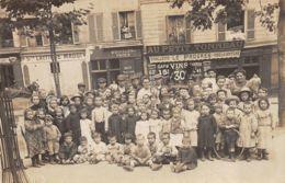 Non Située (Carte Photo) - Groupe D'enfants Et D'adultes Sur Une Place Devant Des Commerces - A Identifier