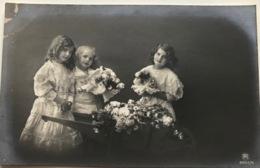 (1186) Een Tweeling En Hun Zusje Bij De Kruiwagen Met Bloemen - Groupes D'enfants & Familles