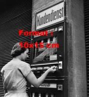 Reproduction D 'une Photographie Ancienne D'une Femme Achetant Des Bas De Nylon Dans Un Distributeur Automatique En 1956 - Reproducciones