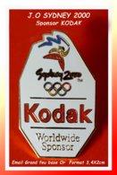 "SUPER PIN'S JEUX OLYMPIQUES SYDNEY 2000 : Worldwide Sponsor ""KODAK"" Photographie, émail Grand Feu Base Or  3,4X2cm - Olympic Games"