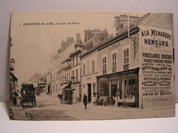 CPA 77 SEINE ET MARNE NEMOURS LA RUE DE PARIS A LA MENAGERE MADAME DIGARD JEUNE FAIENCES PORCELAINES 612 - Nemours