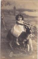 """CARTE FANTAISIE . CPA . """" BONNE ANNEE""""   FILLETTE TOUT SOURIRE """" A CHEVAL""""  SUR UNE CHÈVRE + TEXTE ANNEE 1917 - Portraits"""