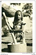 Nigeria. Une Enfant Nigerienne Pilant Le Mil Ou Le Manioc. - Nigeria