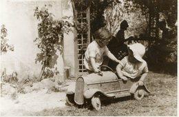 Photo De Deux Petit Enfant Voulant Faire De La Voiture A Pédale Dans Le Jardin - Automobiles
