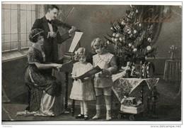 Buon Natale. Couple Jouant De La Musique Et Enfants Chantant Devant Un Sapin De Noel - Nouvel An