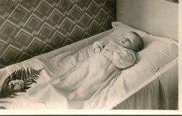 Carte Photo D'un Petit Bébé Sur Sont Petit Lit De Mort Avec Des Fleurs A Ces Pieds - Personnes Anonymes