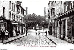 Avranches. Les Commerces De La Rue De La Constitution Et Au Fond Le Monument Aux Morts. - Avranches