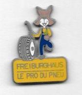 Pin's  Humoristique  Automobile  FREIBURGHAUS, LE  PRO  DU  PNEU  Signé  MAXIMILIEN  PIN' S - Pin