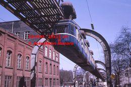 Reproduction D'une Photographie D'une Vue D'en Bas D'un Monorail Schwebebahn à Wuppertal En Allemagne En 1971 - Reproducciones