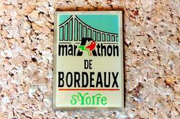Pin's ATHLETISME- Marathon De Bordeaux Publicitaire AUCHAN & SAINT-YORRE - Verni époxy - Fabricant Inconnu - Atletica