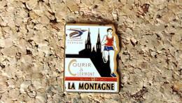 Pin's ATHLETISME - Courir à Clermont-Ferrand Publicitaire Journal La Montagne - Peint Cloisonné - Fabricant Inconnu - Atletica