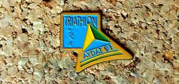 Pin's ATHLETISME - Triathlon Lac D' AYDAT (63) 1991 - Peint Cloisonné - Fabricant Inconnu - Leichtathletik