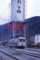 Reproduction D'unePhotographie D'une Vue D'un Train Citerne MC Sous Une Grande Cuve à Martigny En Suisse En 1972 - Riproduzioni