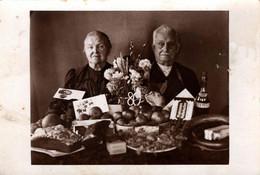 Carte Photo Originale Portrait D'un Couple D'anciens Avec Tous Les Cadeaux Pour Leurs 80 Ans - Pommes, Hennessy, Gâteaux - Persone Anonimi