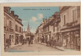 Auzances  23   La Rue De La Poste Tres Tres Animée -Coiffeur-Tabac-Journaux-Cycles-Café-Epicerie Et Voiture - Auzances