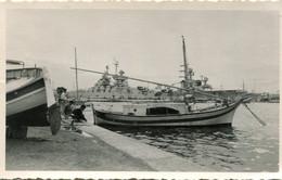 Grande Photo D'un Petit Port Avec De Petit Bateau De Péche En Bois Et A L'arrière Un énorme  Navire De Guerre - Barche