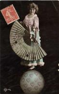 Jeune Femme En équilibre Sur Un Ballon Portant Un Eventail Geant RV - Donne