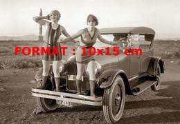 Reproduction Photographie Ancienne De Deux Jeunes Femmes En Robe Courte Debout Sur Le Pare Choc D'une Automobile - Reproductions